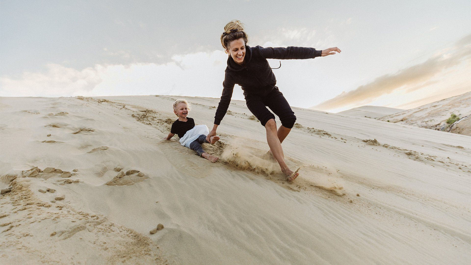 A mother runs down a sand dune, pulling her son along, both of them laughing. Photo by Christian Anderl.